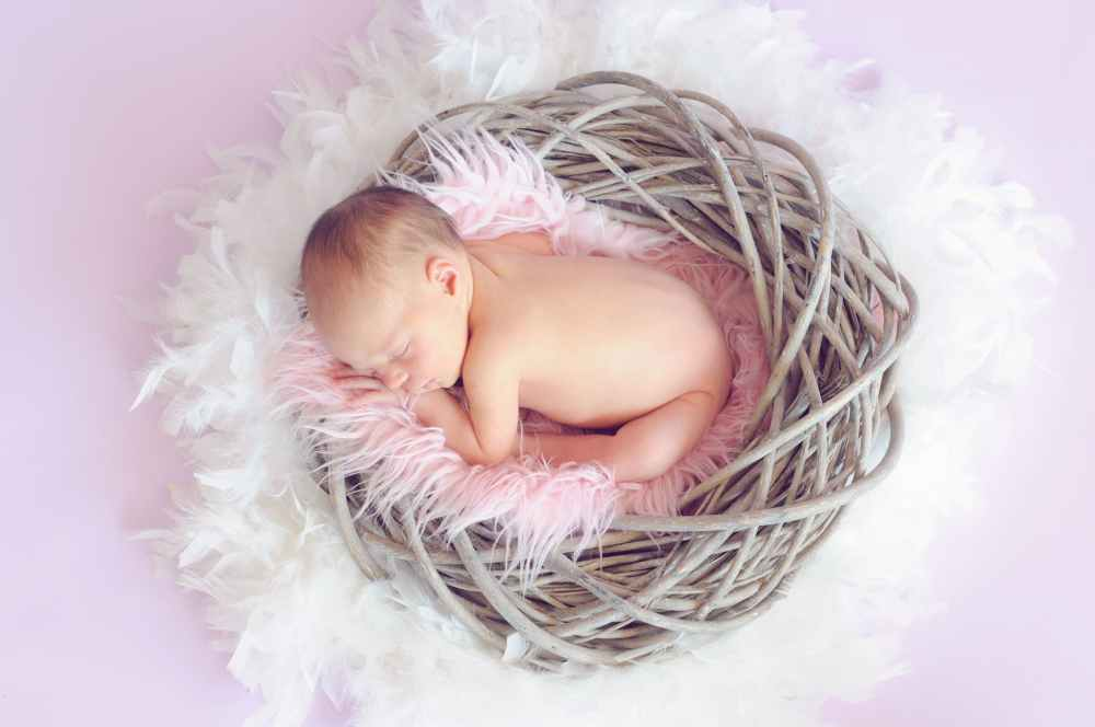 baby sleeping in a basket and a round feather surrounding the basket
