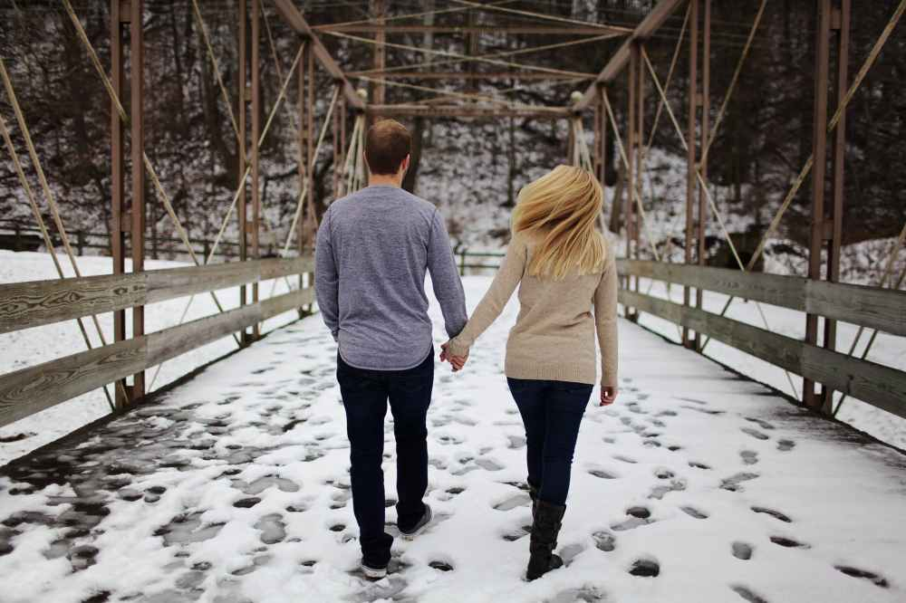 man and woman walking on snow covered road