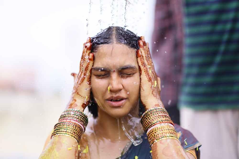 woman taking shower while wearing sari dress