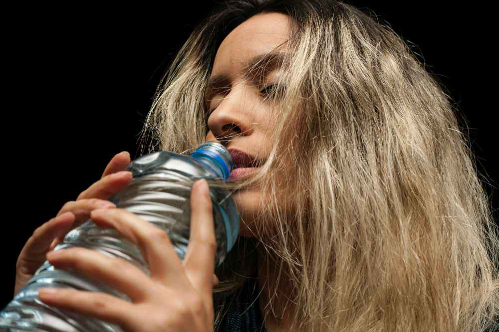 woman holding blue plastic bottle