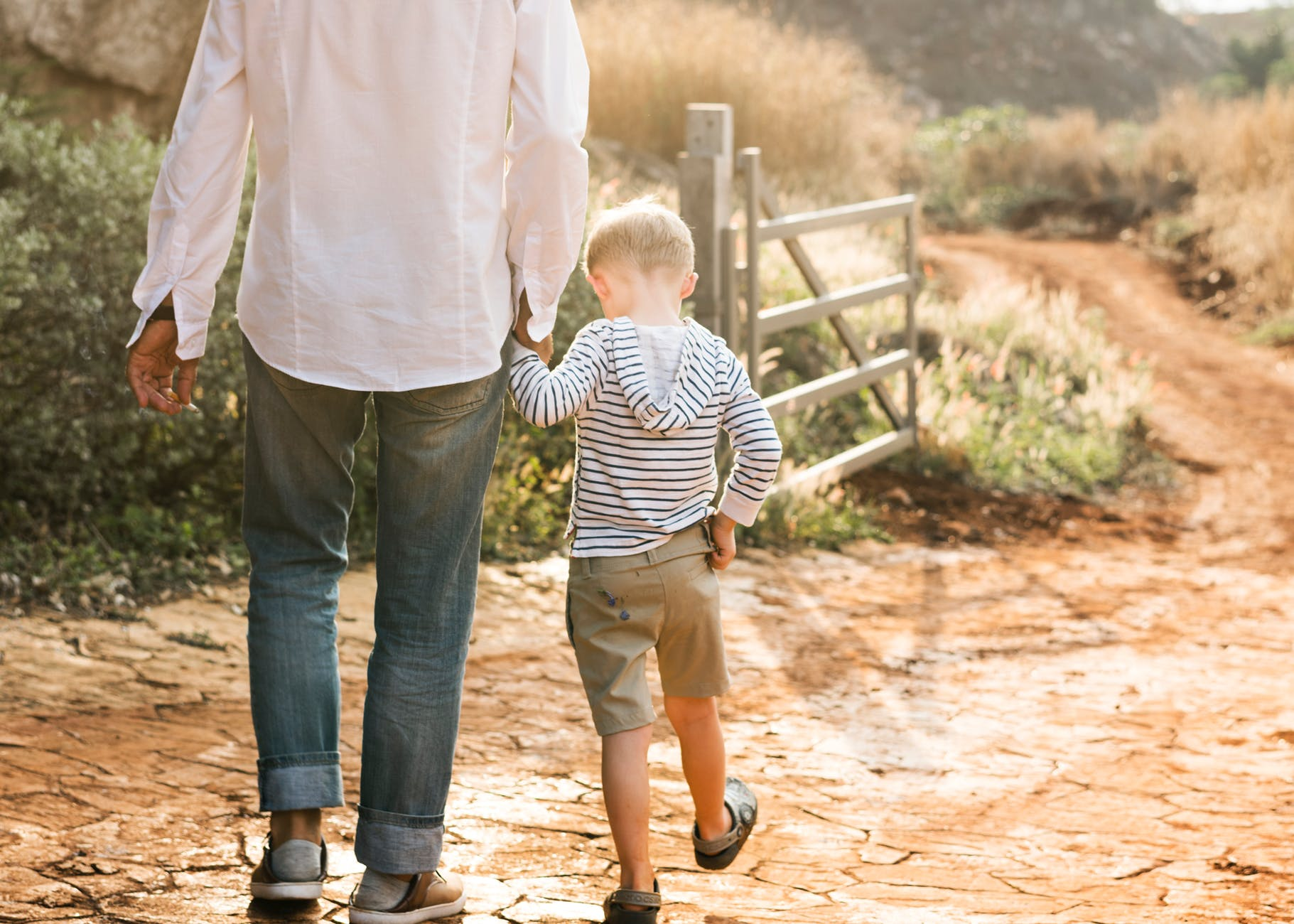 man in white shirt walking with boy near wooden fence gate