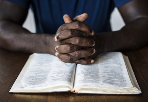 Black-Hands-on-Bible-1 Photo from Unsplash