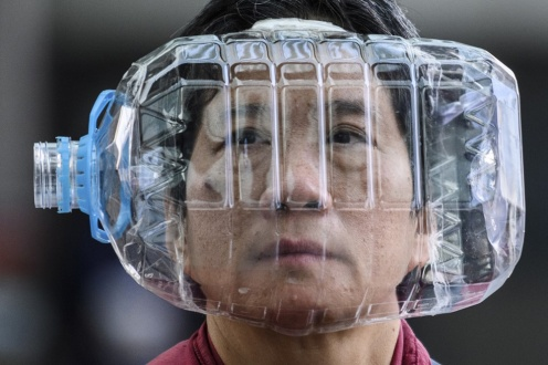 "A woman wears a plastic water bottle with a cutout to cover her face, as a preventative measure following a virus outbreak which began in the Chinese city of Wuhan, while walking on a footbridge in Hong Kong on January 31, 2020. - The World Health Organization, which initially downplayed the severity of a disease that has now killed 170 nationwide, warned all governments to be ""on alert"" as it weighed whether to declare a global health emergency. (Photo by Anthony WALLACE / AFP)"