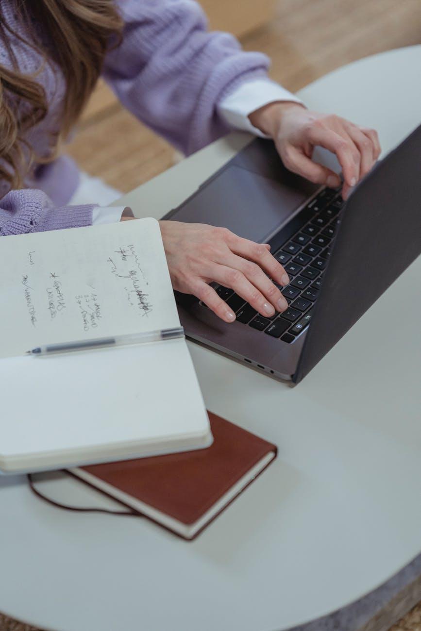 crop woman typing on laptop
